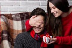 Kvinnan gör en överraskning till mannen Julfilial och klockor Arkivfoton