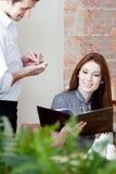 Kvinnan gör en beställning Arkivfoto