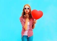 Kvinnan gör en luft att kyssa med en röd ballong i formen av en hjärta Arkivfoton