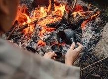 Kvinnan gör ett kaffe på lägereld Arkivbild