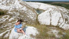 Kvinnan gör ett plan i anteckningsboken i naturen stock video