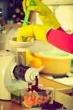 Kvinnan gör grönsakfruktsaft i juicermaskin Royaltyfri Foto