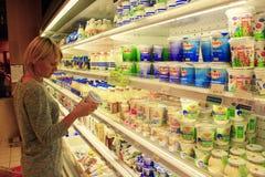 Kvinnan gör hennes val i shoppa av mejeriprodukter royaltyfri bild