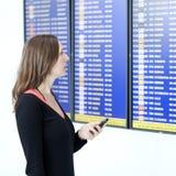 Kvinnan gör incheckningen med smartphonen på flygplatsen Arkivfoto