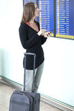 Kvinnan gör incheckningen med smartphonen på flygplatsen Fotografering för Bildbyråer