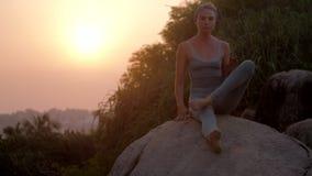 Kvinnan gör kondition på enormt vaggar på soluppgångultrarapid arkivfilmer