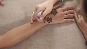 Kvinnan gör kroppkonst vid henna på händer av flickan, närbild från överkant lager videofilmer