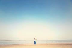 Kvinnan gör meditationövningar som vänder mot havet royaltyfri fotografi