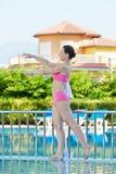 Kvinnan gör morgonövningar på poolside Arkivfoto