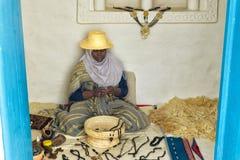 Kvinnan gör neckaces vid handen i Djerba, Tunisien arkivbild