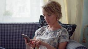 Kvinnan gör online-betalning vid kreditkorten arkivfilmer