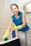 Kvinnan gör ren badrummet Arkivfoto