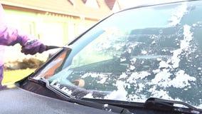 Kvinnan gör ren bilfönstret från snön och is med en skrapa arkivfilmer