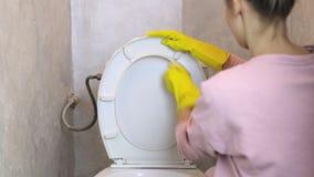 Kvinnan gör ren den vita toalettbunken med en svamp i gula gummihandskar lager videofilmer