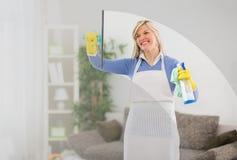 Kvinnan gör ren fönstret i hus royaltyfri foto