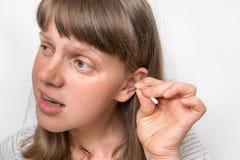 Kvinnan gör ren hennes smutsiga öron med bomullsbomullstoppen royaltyfri fotografi