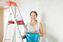 Kvinnan gör reparationer hemmastadda Royaltyfria Bilder