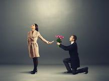 Kvinnan gör se inte mannen med blommor Royaltyfri Fotografi