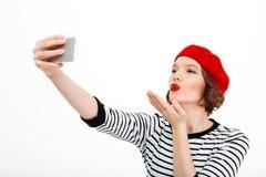 Kvinnan gör selfie vid mobiltelefonen som blåser kyssar Arkivbilder