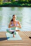 Kvinnan gör utomhus- yoga Öva för kvinna som är livsviktigt, och meditation för konditionlivsstilklubba på naturbakgrunden arkivbild
