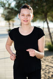 Kvinnan 20-30 gamla år joggar i svart T-tröja Arkivbilder
