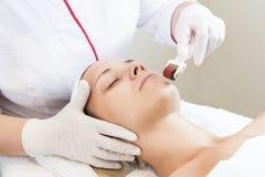 Kvinnan genomgår tillvägagångssättet av medicinsk mikrovisarterapi med en modern dermarulle för medicinskt instrument royaltyfria bilder