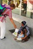Kvinnan ger sig till tiggarekvinnan som mat för henne behandla som ett barn Arkivfoto