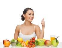Kvinnan ger upp tummar med frukter och grönsaker Royaltyfri Fotografi