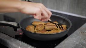 Kvinnan grillar pannkakor med fyllningar på en panna i hennes inhemska electro spis, närbild av händer lager videofilmer