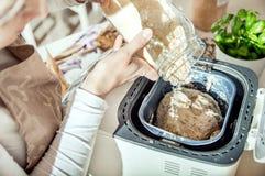 Kvinnan häller ingredienser in i maskinen för brödtillverkaren Royaltyfri Bild