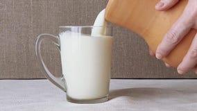 Kvinnan häller mjölkar från en kanna in i ett exponeringsglas arkivfilmer