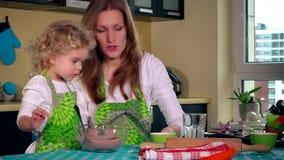Kvinnan häller olja in i kakadeg och den lilla hjälpredadotterflickan som blandar med skeden arkivfilmer