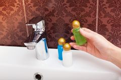 Kvinnan häller schampo in i hennes hand Royaltyfri Fotografi