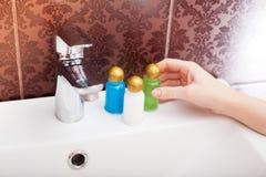 Kvinnan häller schampo in i hennes hand Royaltyfria Bilder