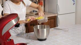 Kvinnan häller sirap i blandarebunke för att laga mat kräm för kaka arkivfilmer