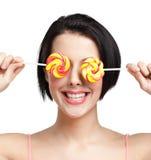 Kvinnan håller lollypops på ögonen royaltyfria bilder