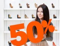 Kvinnan håller modellen av den 50% försäljningen på pumpar Royaltyfri Bild