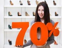 Kvinnan håller modellen av den 70% försäljningen på pumpar Royaltyfria Bilder
