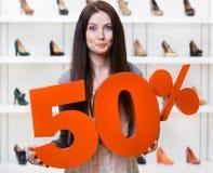 Kvinnan håller modellen av den 50% försäljningen på skodon Arkivbilder