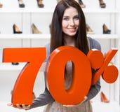 Kvinnan håller modellen av den 70% försäljningen på skodon Royaltyfria Foton