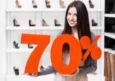 Kvinnan håller modellen av den 70% försäljningen på skor Royaltyfri Foto