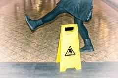 Kvinnan halkar nästan på ett vått golv arkivbild