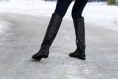 Kvinnan halkar på den hala vägen som täckas med is Begrepp av skadarisken i vinter Arkivfoto