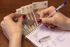 Kvinnan hand-skriver kostnaderna i en anteckningsbok Arkivfoto
