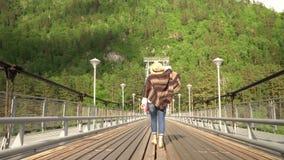 Kvinnan handelsresanden går vidare denblivna bron till och med bergfloden stock video