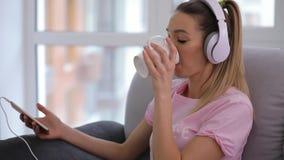 Kvinnan har att koppla av hemma med kopp te och bra musik i hörlurar lager videofilmer