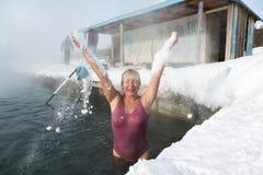 Kvinnan har ett termiskt bad i pöl för varm vår Arkivfoto