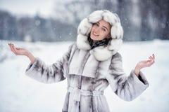 Kvinnan har gyckel på den insnöade vinterskogen royaltyfri foto
