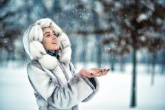 Kvinnan har gyckel på den insnöade vinterskogen Arkivfoto