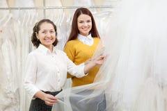 Kvinnan hjälper bruden, i att välja som är brud- att skyla Arkivfoto